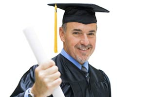 A man in a cap and gown holding a diploma