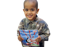 A child smiling while holding a book