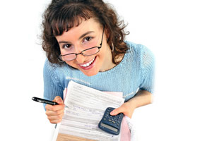 A woman holding tax forms and a calculator