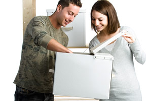 A woman and man putting an item into a box