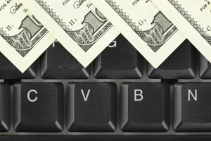 Dollar bills lay on top of keyboard
