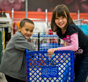 Two kids sit in shopping cart