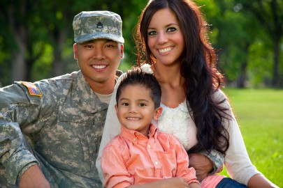 Young American soldier in army combat uniform with wife and son in a park.